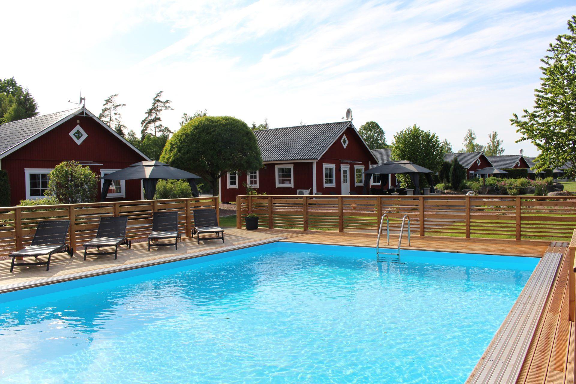 Röda stugor med uteplats och pool Småland